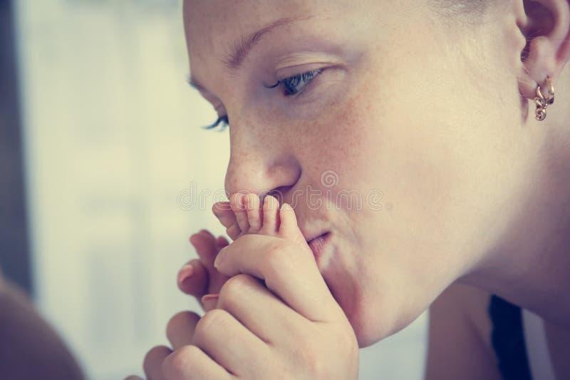 Modern som kysser henne, behandla som ett barn fot som symboliserar mjukhet och, att bry sig fotografering för bildbyråer