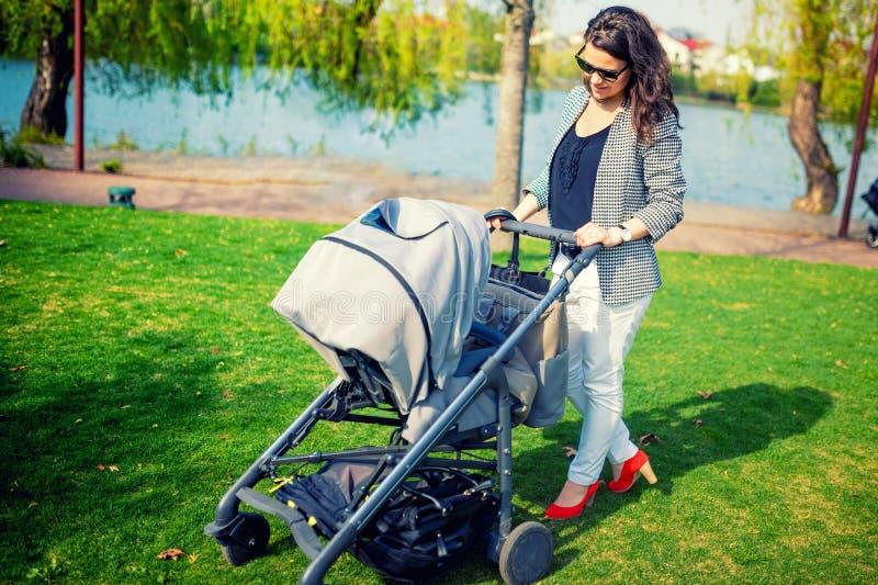 Modern som ler med, behandla som ett barn parkerar in Fostra att gå barnet med pramen eller behandla som ett barn sittvagnen royaltyfri bild