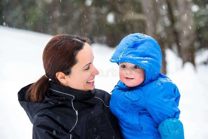 Modern som ler på, behandla som ett barn sonen utanför i vintern royaltyfria foton