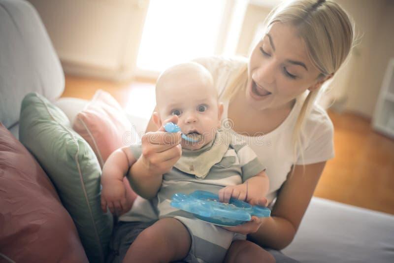 Modern som matar hennes litet, behandla som ett barn pojken hemma royaltyfri fotografi