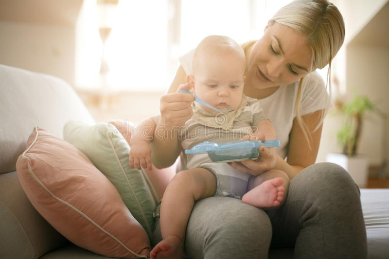 Modern som matar hennes litet, behandla som ett barn pojken hemma royaltyfri bild
