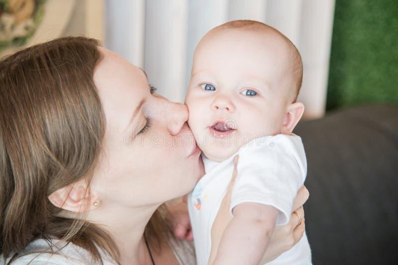 Modern som rymmer henne, behandla som ett barn sonen som kysser fotografering för bildbyråer