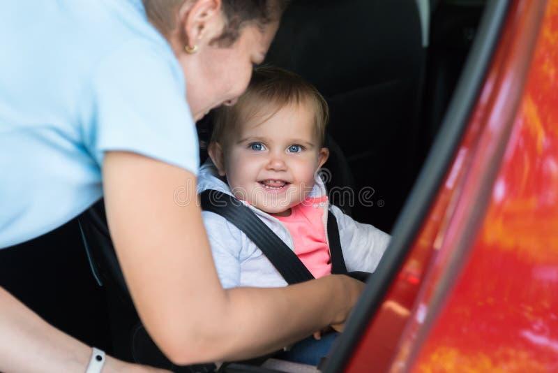 Modern som tar omsorg av henne, behandla som ett barn i bil royaltyfri fotografi