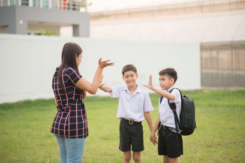 Modern som tillsammans tar söner till skola, handvågen, säger farväl royaltyfri foto