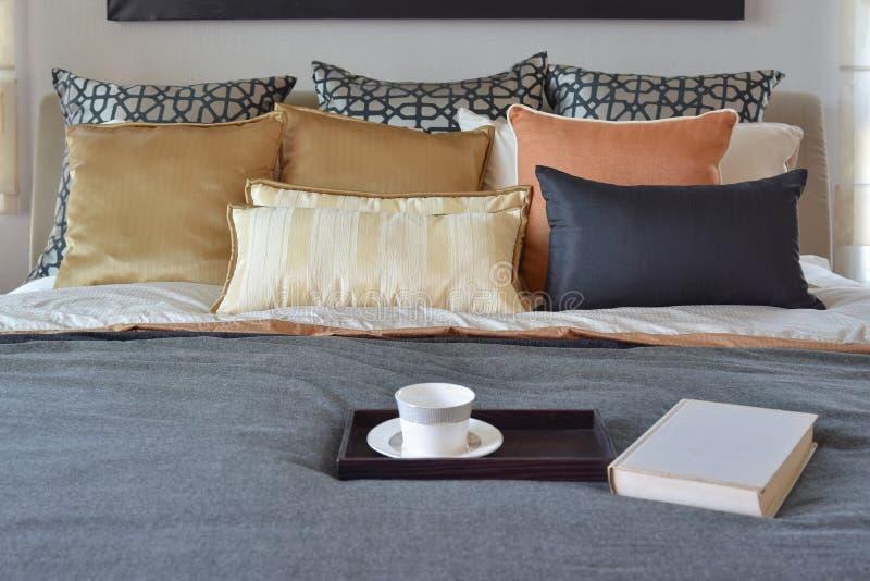 Modern sovruminre med tekoppen på det dekorativa trämagasinet på säng arkivfoton