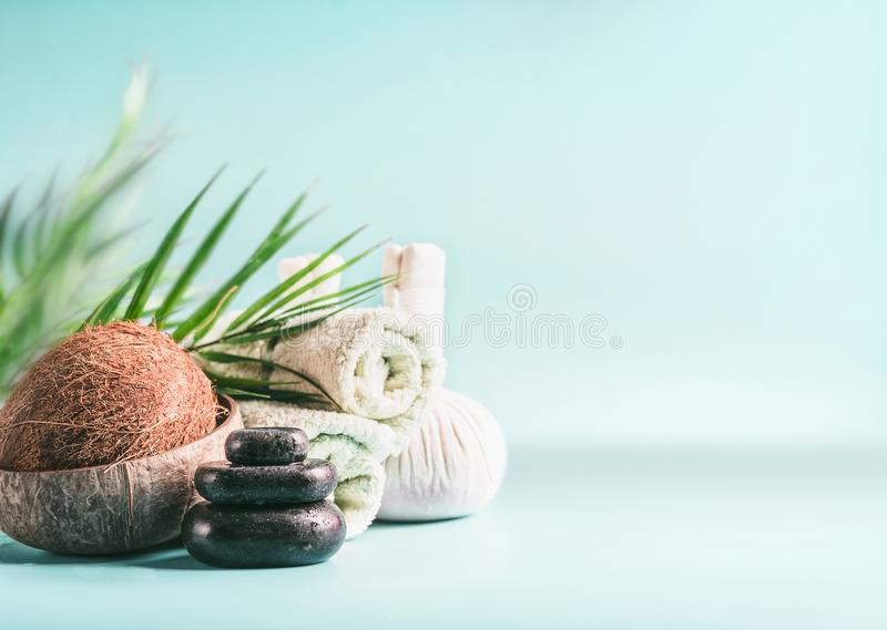 Modern spa setting with coconut and palm leaves. Massage equipment : stack of massage stones, herbal stamps setting and rolled royalty free stock photos