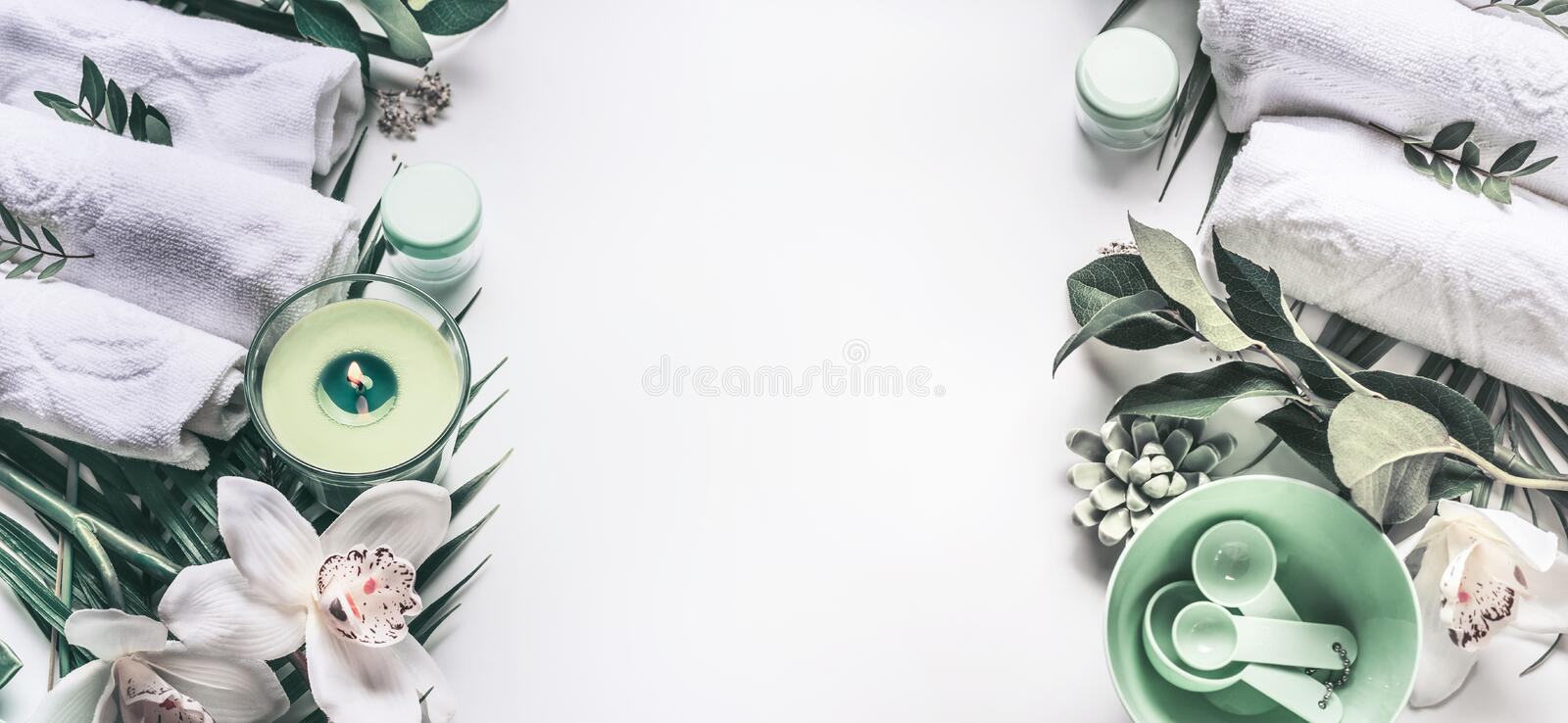 Modern Spa setting with towels, tools, candle, green tropical leaves, orchid flowers on white background with copy space , top vie royalty free stock photos