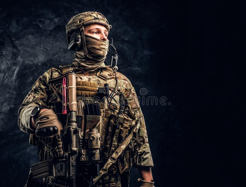 Modern special forces soldier in camouflage uniform looking sideways. Studio photo against a dark wall. stock images