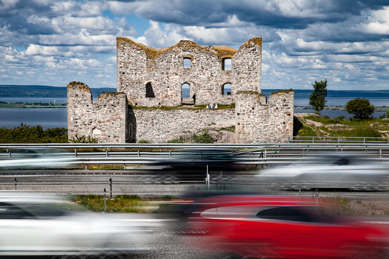 Modern speedy cars and an old ruin. An old ruin, the Brahehus, is located between a highway with a lot of trafic and an idyllic lake Vattern in Sweden