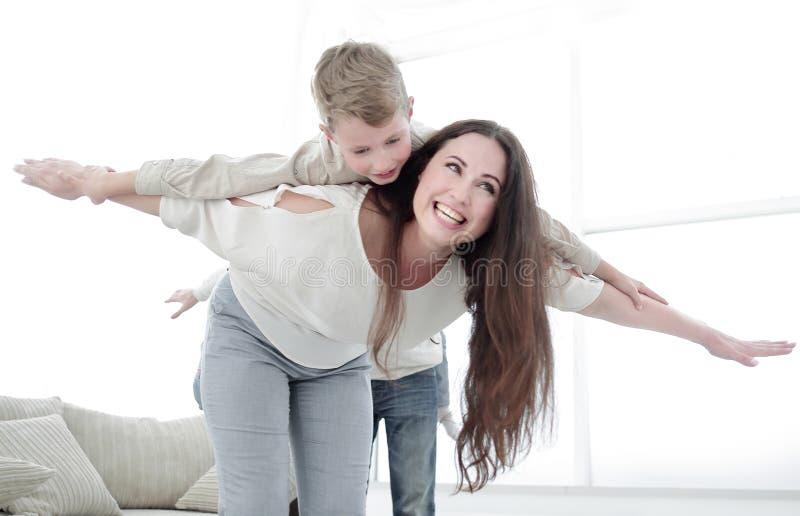 Modern spelar med hennes son i en rymlig vardagsrum royaltyfria foton