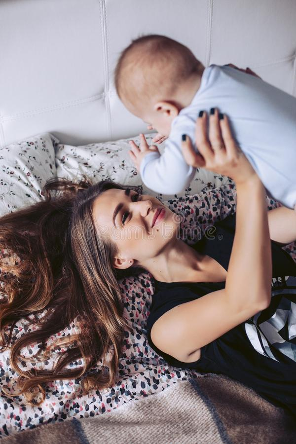 Modern spelar med småbarnet som ligger på en säng fotografering för bildbyråer