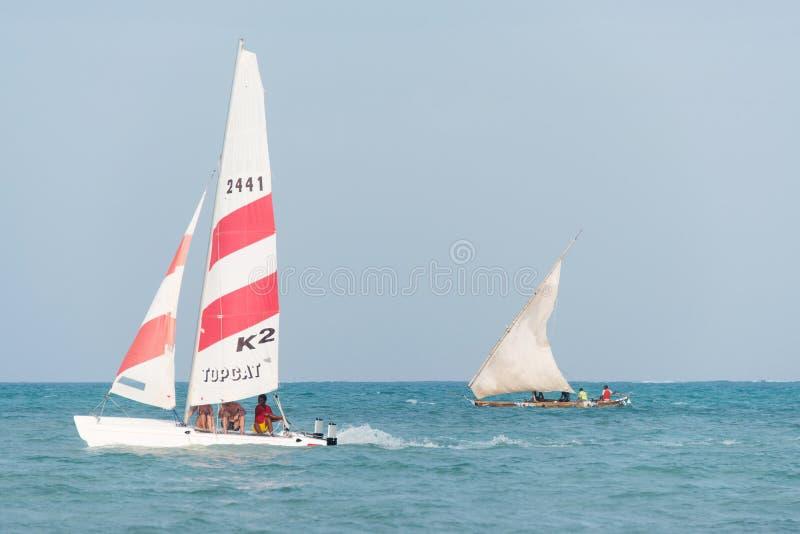 Modern sport catamaran and traditional wooden dhow boat sailing near Jambiani beach, Zanzibar royalty free stock images