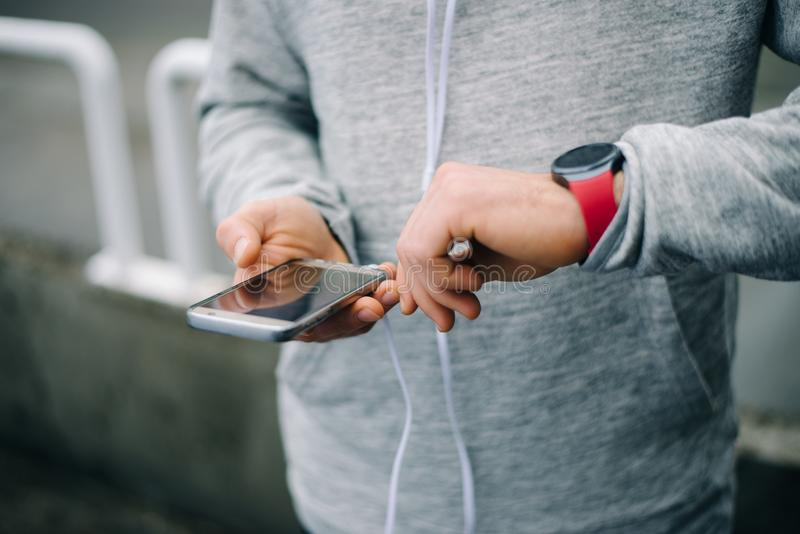 Runner using sporty smart watch and smartphone for training stock photography