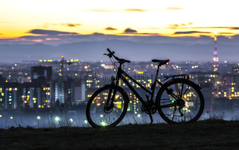 Modern sports city bicycle standing alone over night city background. With many bright lights. View of orange sunset sky in Ivano Frankivsk city, Ukraine with stock photography