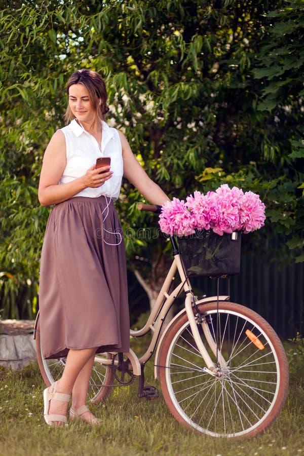 Modern står med en cykel royaltyfri bild