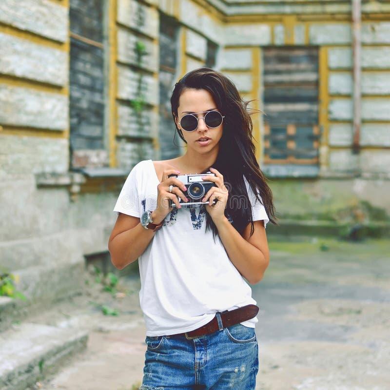 Modern stads- flicka med den utomhus- tappningfotokameran arkivfoton