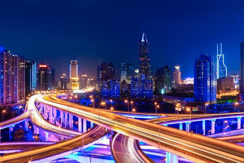 Modern stadshorisont med utbytesplanskilda korsningen på natten royaltyfria bilder