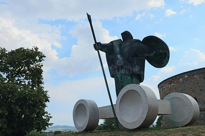 Modern statue of hungarian warrior with spear and shield, with stone cart shaped pedestal, placed in front of Esztergom castle. Hungary stock images