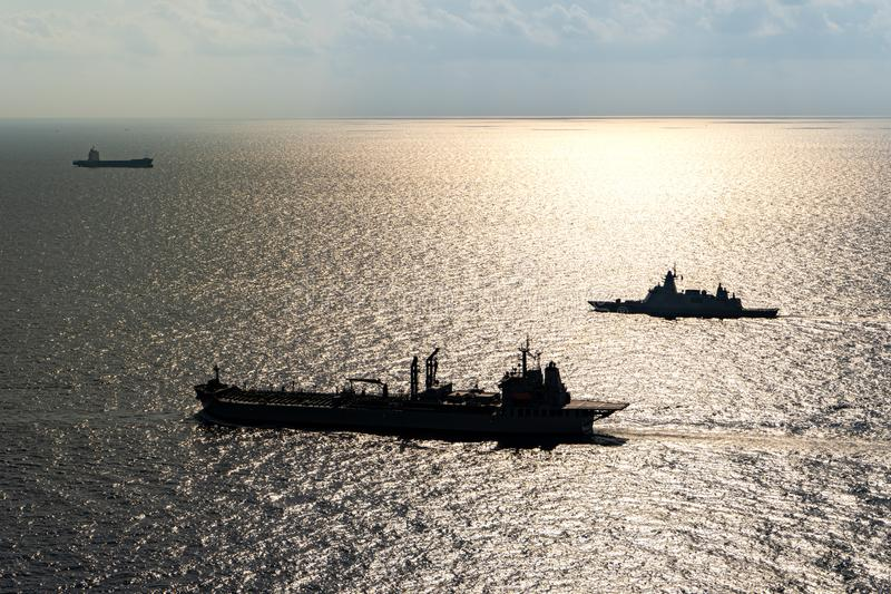 Modern stealth frigate and fleet replenishment vessel  sail in the sea for maritime security activity stock image
