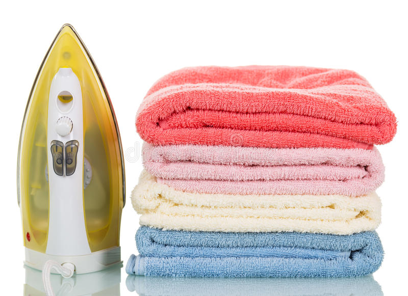 Modern steam iron and stack towels isolated on white background. Modern steam iron and stack of towels isolated on white background stock photo