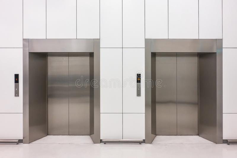 modern steel elevator cabins with closed doors at business lobby royalty free stock image