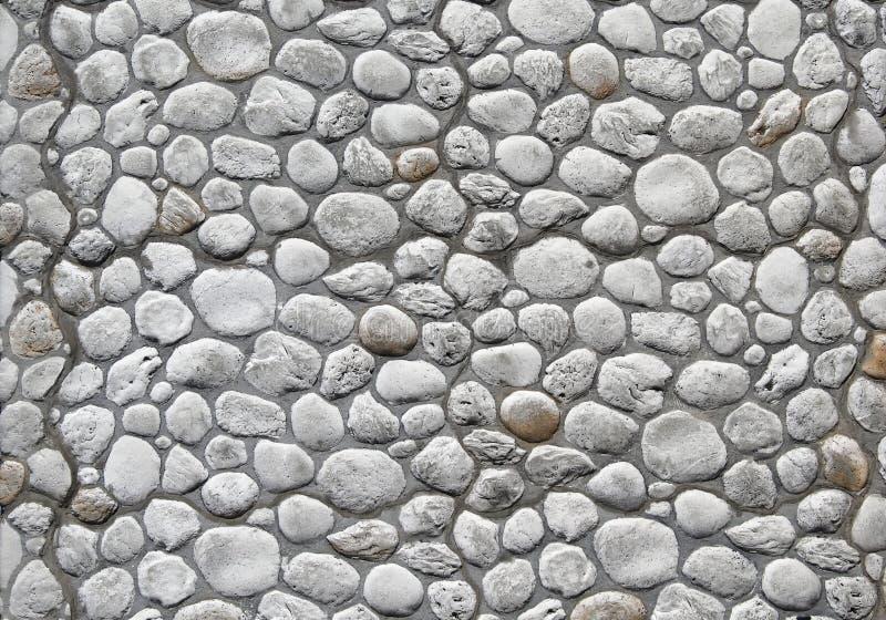Modern stenvägg i medeltida stil med stora runda vita naturliga stenar royaltyfria foton