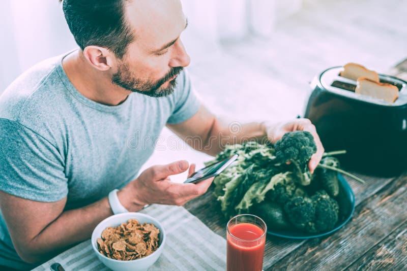 Modern stilig man som gör ett foto av broccoli arkivfoton