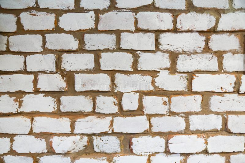 Modern stone brick wall background inside Cafe. White bricks with brown seams. Stone texture royalty free stock photography
