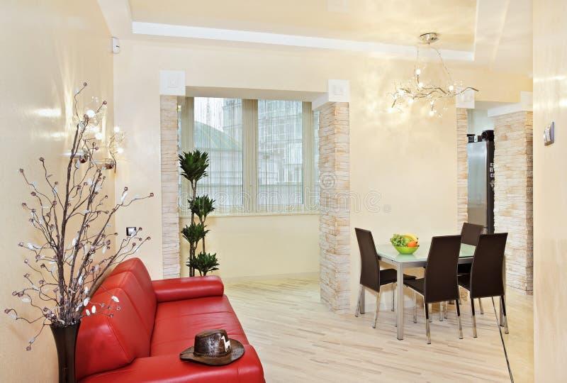 Modern studio interior with red sofa. Modern studio interior in warm tones with red sofa royalty free stock image