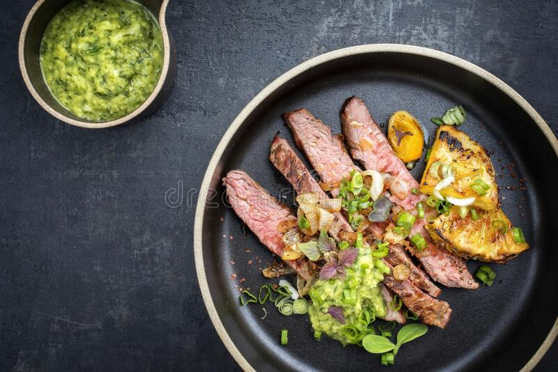 Modern style barbecue dry aged wagyu flank steak with pineapples and chimichurri sauce on a design plate stock photography
