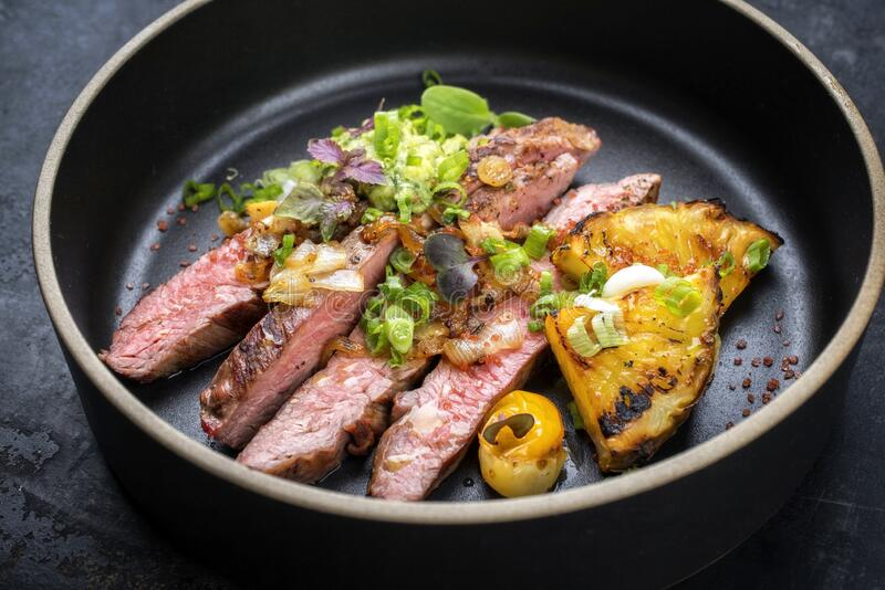 Modern style barbecue dry aged wagyu flank steak with pineapples and chimichurri sauce on a design plate stock photo