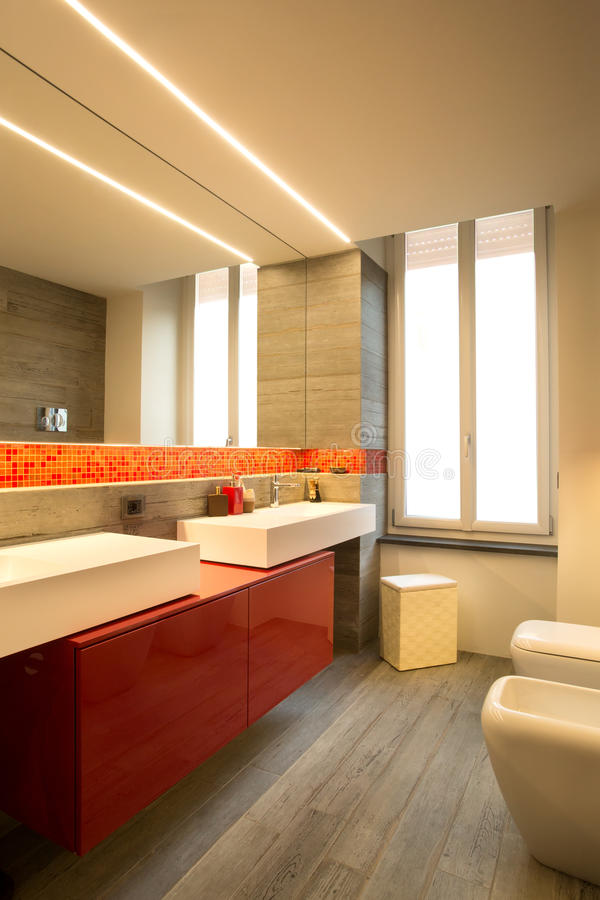 Modern style bathroom with double sink, warm colors. Modern style bathroom with double sink, large mirror and wall lightning royalty free stock photos