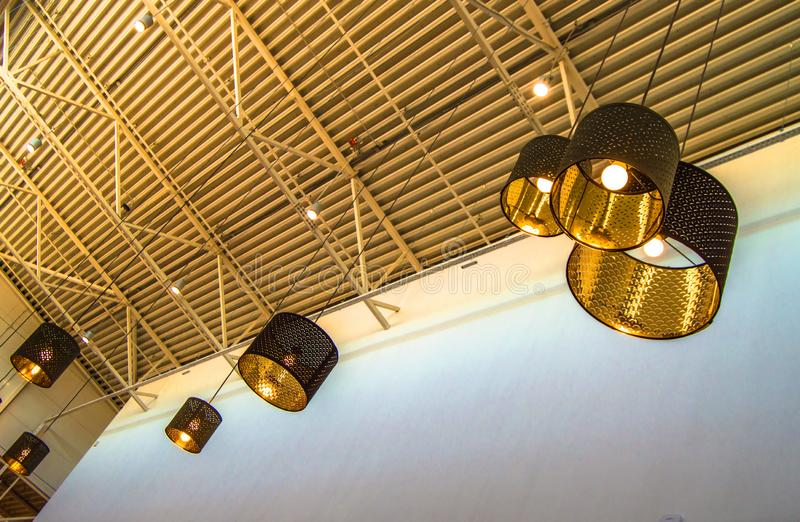 Modern style bronze decorative lamps and Golden lampshades hang on a long rope, industrial ceiling, interior design royalty free stock photos