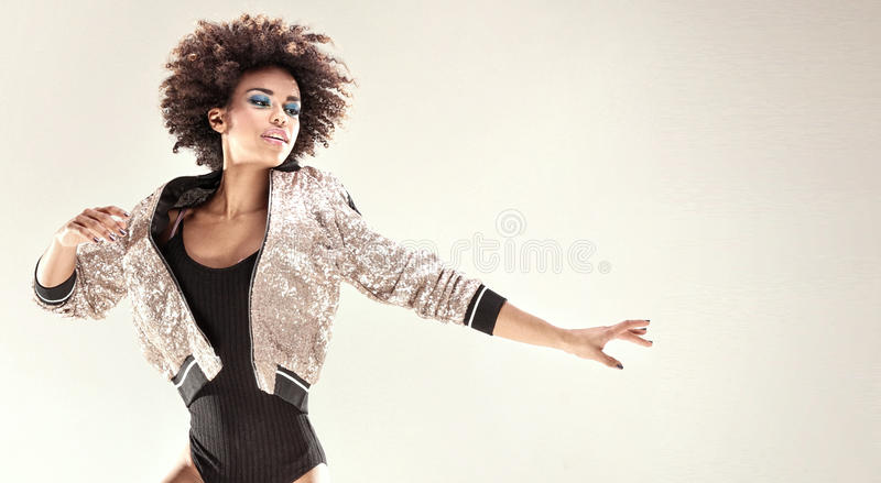 Modern style dancer in studio. Modern style dancer with afro on her head jumping in studio royalty free stock photography