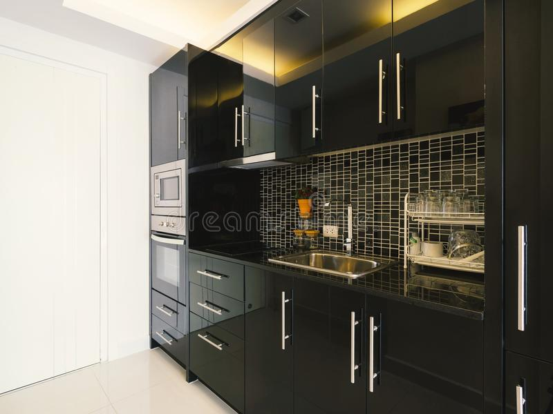 Modern style kitchen with stainless steel appliances. Modern style kitchen interior in modern home with black color ceramic and stainless steel appliances stock images