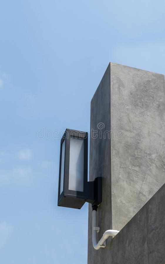 Modern style lamps on polished concrete loft wall. On blue sky background stock images