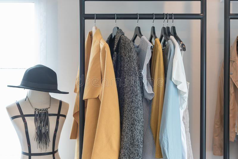 Modern style wardrobe with clothes. Hanging on railing steel, in modern walk in closet, interior design concept royalty free stock photos