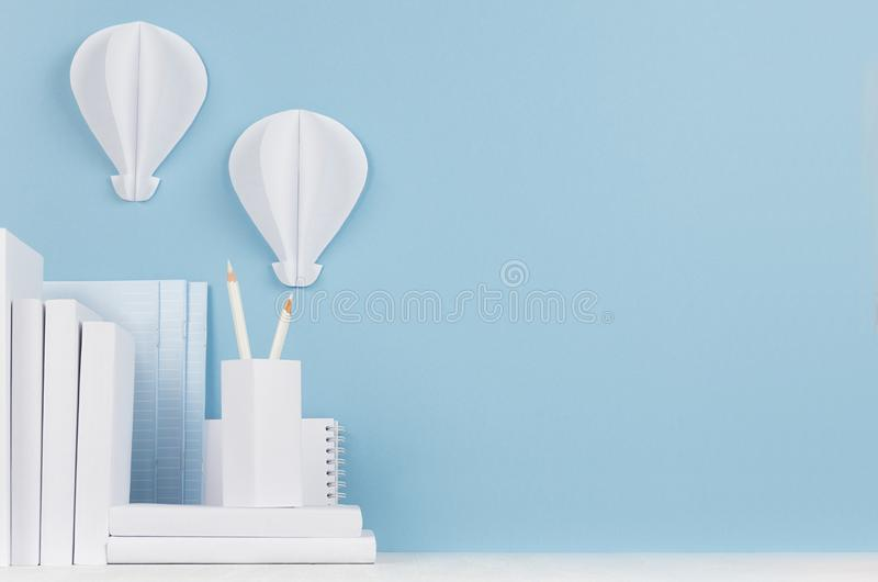 Modern style workplace - white stationery and decorative paper balloons on soft blue background and light desk. royalty free stock photo