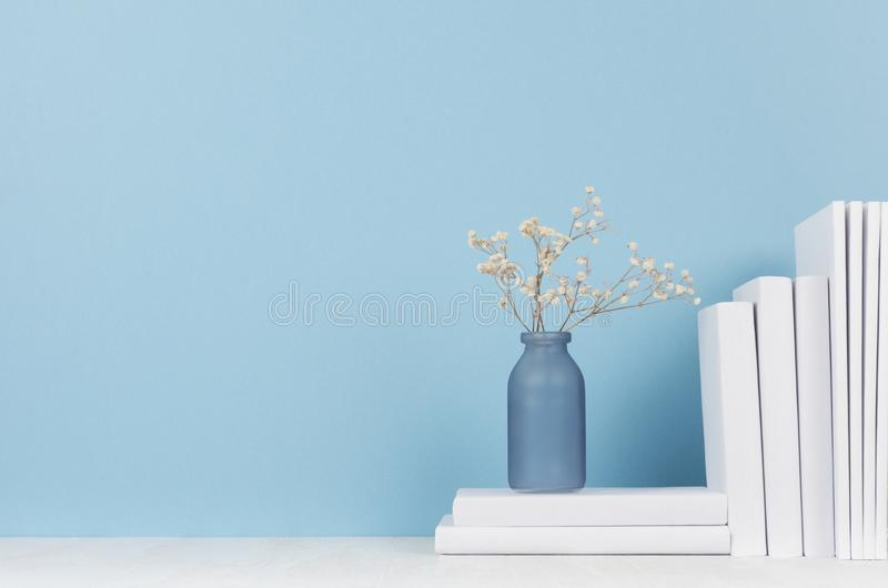 Modern style workplace - white stationery and glass vase with dry flowers on soft blue background and light desk. Modern style workplace - white stationery and stock photo