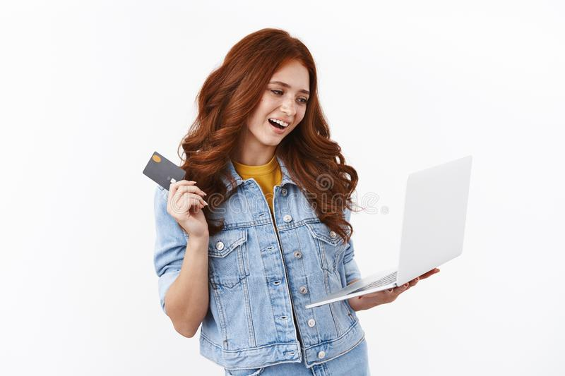 Modern stylish girl pick new outfit internet store, shopping online, hold laptop and waving black credit card with. Delighted, satisfied grin, input bank stock photo