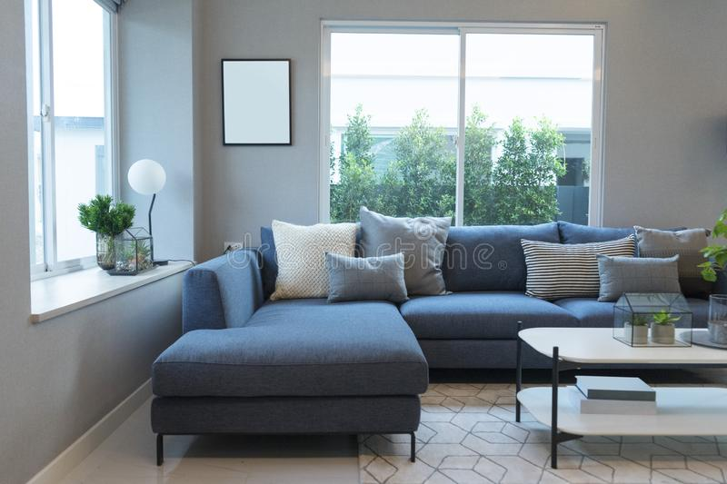 Modern and stylish living room, blue sofa and grey pillow with coffee table royalty free stock photography