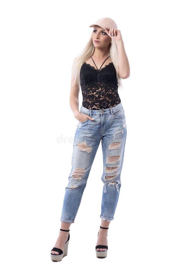 Modern stylish trendy girl looking up thinking and holding cap visor. Full body isolated on white background royalty free stock images