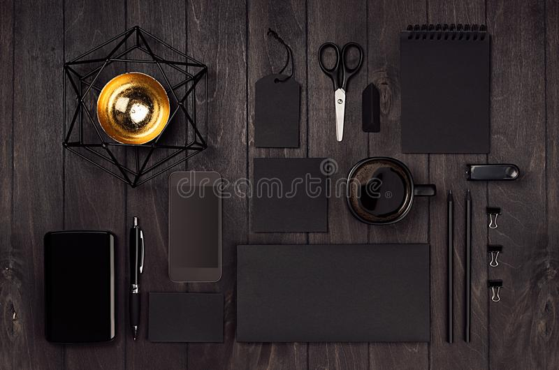 Modern stylish working place with blank black stationery, phone, coffee, gold decor on dark wood board. royalty free stock photos