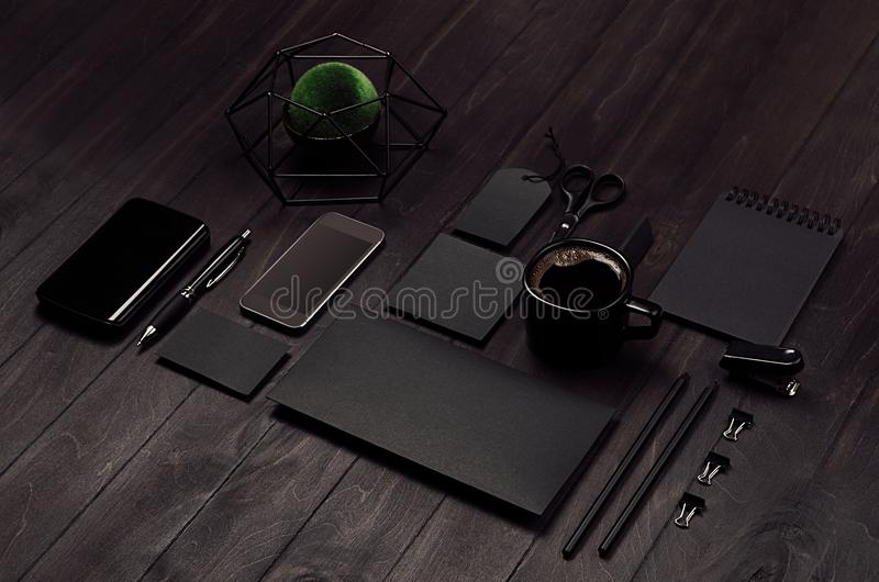 Modern stylish working place with blank black stationery, phone, coffee, green plant on dark wood board, inclined. royalty free stock photography