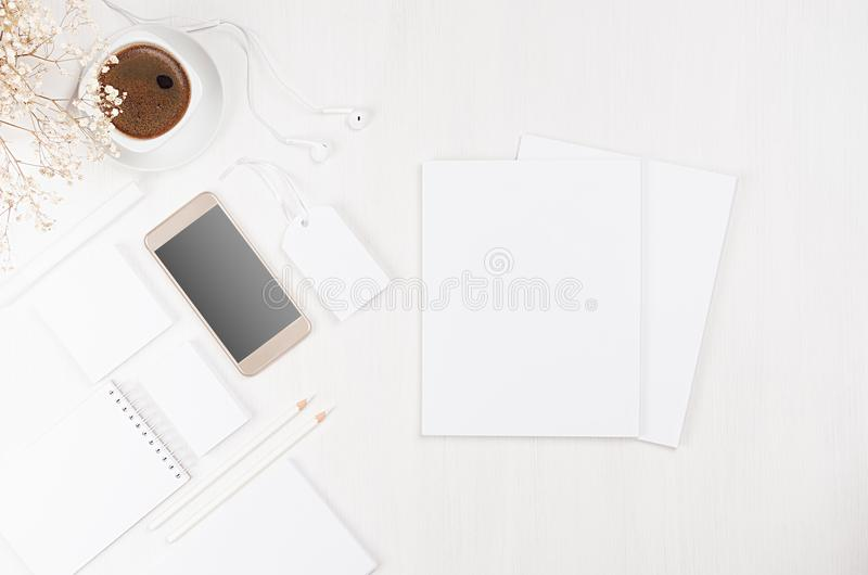 Modern stylish working place with blank white stationery, brochure, phone, coffee, flowers on soft white wood board. stock photos