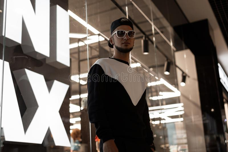 Modern stylish young hipster man with a beard in a black cap in sunglasses in a fashionable sports suit is standing. Near the bright glass wall in the shopping royalty free stock photos