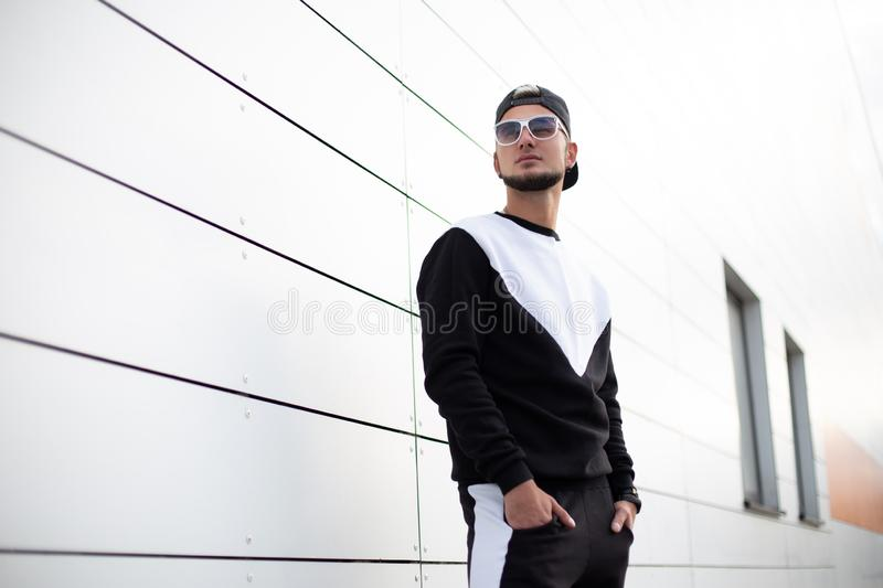Modern stylish young hipster man with a beard in a black cap in sunglasses in a fashionable sports suit is standing. Near the white wall in street. Attractive royalty free stock images