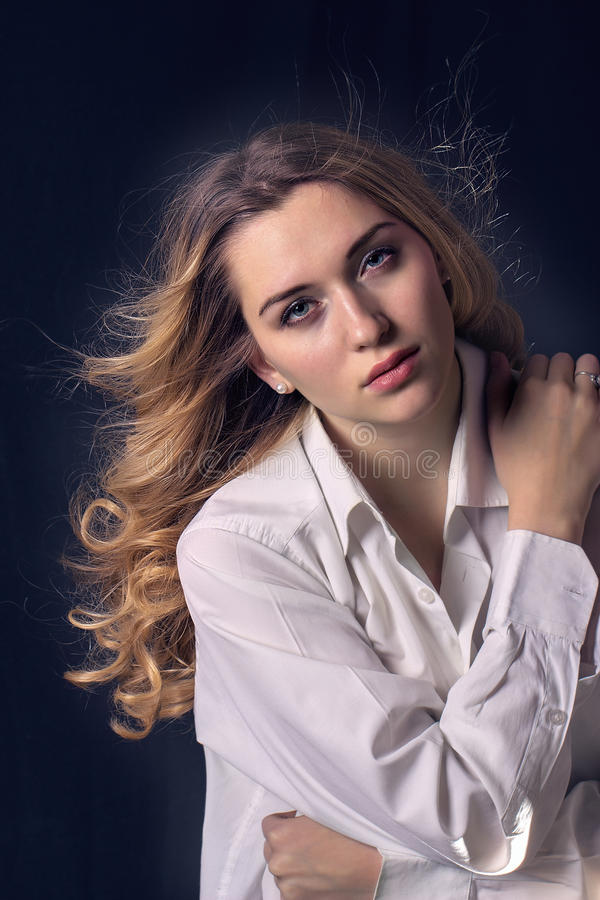Modern stylish young woman model standing on a dark background royalty free stock images