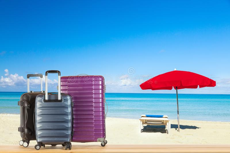 Modern suitcases baggage for travelling or business trip on wooden floor against amazing beach ocean coast background with sun. Lounger under red umbrella stock photo