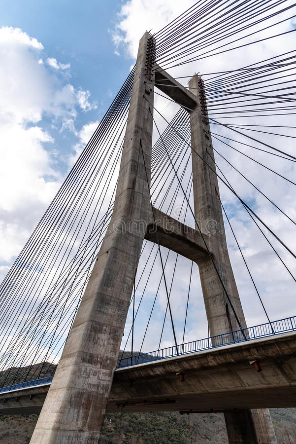 Modern suspension bridge. Detail of tower and steel cables royalty free stock image